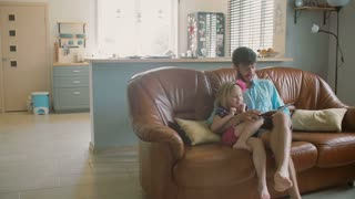A young handsome father is sitting on the sofa reading a book to his precious little daughter. Slow mo, Steadicam shot