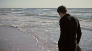 A young man is walking along beautiful beach on a windy day carrying his shoes in his hands.
