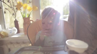 Adorable, cute little boy sitting in high chair, eating, laughing and smiling in sun rays in front of big window