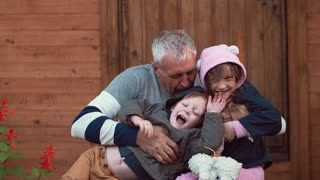 An ageing man is having great time with his grandchildren. He hugs them, they run around happily, laugh. Slow mo