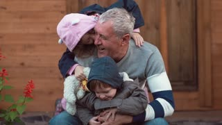 An ageing man is having great time with his grandchildren. He hugs them, they run around happily. Slow mo