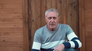 An ageing man sits near a wooden house and looks into camera. Slow mo