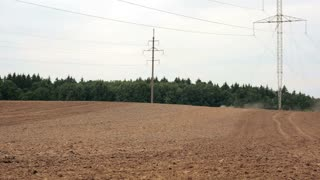 An agricultural tractor, plowing a field, appears in the distance, becomes visible, moves to the camera.