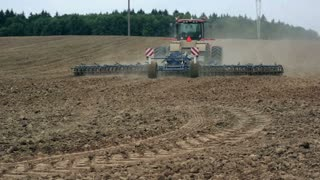 An agricultural tractor, plowing a field before sowing, moving from the camera. A forest in the background.