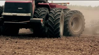 An agricultural tractor, plowing a field before sowing, turning backwards in front of the camera. close-up