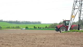 An agricultural tractor plowing a field. Hills and a forest at the background.
