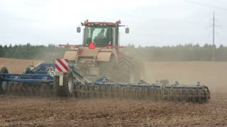 An agricultural tractor, plowing a field, moving from the camera. Soil dust.