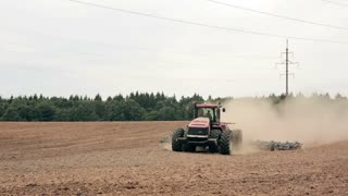 An agricultural tractor, plowing a field, moving to the camera. A forest in the background.