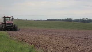An agricultural tractor plowing a field, moving to the camera.