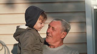 An old man holds a little cute boy on his hands, looks at him. The boy points on something with his finger. Slow mo
