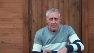 An old man sits near a wooden house, looks into camera and smokes. Slow mo