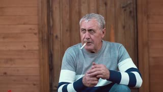 An old man with grey hair sitting near a house lights up his cigarette, smokes and looks into camera. Slow mo