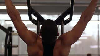 Athletic man is exercising during workout in the gym. Man is doing pull ups in gym with exercise equipment.