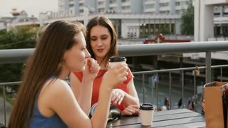 Attractive brunette women drinking coffee communicate in a cafe with a view of the traffic, talking after shopping. 4k
