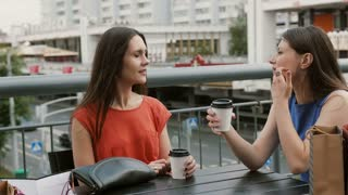 Attractive women friends communicate in a cafe with a view of the traffic, talking, drinking coffee after shopping. 4k