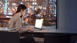 Attractive young businesswoman working on laptop sitting at the bar, outside winter night city decorated for Christmas