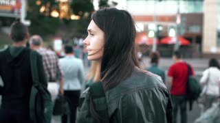 Attractive young woman crossing street in the city at a crosswalk. Slow motion, steadicam shot, back view.