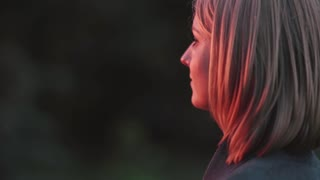 Attractive young woman standing at park in the rays of the setting sun and looking into the distance. Close-up Side view