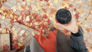 Autumn. Top view of young stylish woman with smart watches drinking coffee. fallen beautiful maple leaves 4k