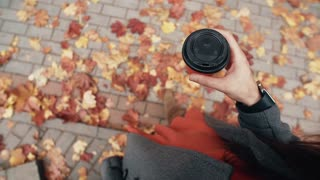 Autumn. Top view of young stylish woman with smart watches holding cup of coffee. fallen beautiful maple leaves 4k