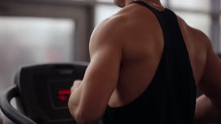 Back and side view of a strong bodybuilder running on a treadmill while working out in a sport club. Healthy lifestyle.