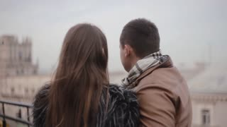 Back and side view of lovers on a roof enjoying the city view. They kiss, talk smile to each other. Cold foggy weather.