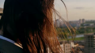 Back view. close-up Wind blows long dark hair beautiful young women. girl standing on the roof at sunset. Slow mo