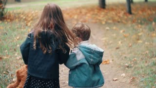 back view cute brother and sister little boy and girl running holding hands with their toys through autumn alley slow mo