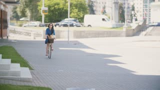 Back view of a beautiful brunette girl riding a bike near busy road with driven cars, slow mo