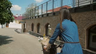 Back view of a girl in a dress riding a bike with flowers in a basket touching tree leaves, slow mo, steadicam shot