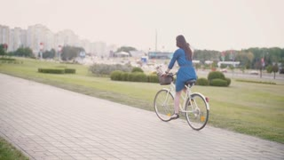 Back view of a girl riding a bike with flowers and French bread in a basket in the city, slow mo, steadicam shot