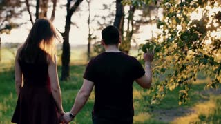 Back view of a happy couple walking in the forest holding hands at the sunset. Slow mo, steadicam shot