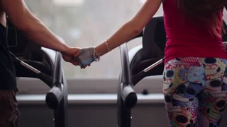Back view of a sporty couple running on treadmills holding hands. Close-up of hands. Working out in a gym.