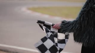 Back view of a woman is holding a waving race checkerd flag. Go-kart track.