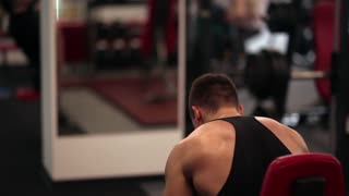 Back view of an athletic man sitting on a chair resting. Sporty man is having a break after a workout in the gym.