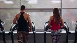 Back view of athletic man and beautiful woman walking on treadmills, talking and smiling. Work out in a sport club.