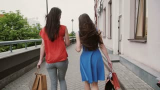 Back view of beautiful young women walking past the shops, with shopping bags, talking discuss, slow mo stedicam shot