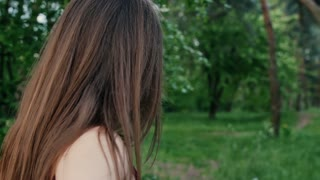 Back view of brunette girl with long hair walking in garden or forest, touching leaves of trees. Slow mo, steadicam shot