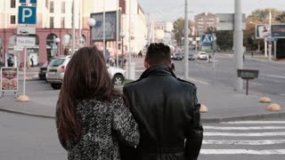 Back view of happy lovers walking in the street. Beautiful girl looks back into camera smiling. Slow mo, steadicam shot