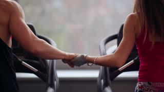 Back view of sporty man and beautiful woman running on treadmills, holding hands. Work out in a sport club. Close-up