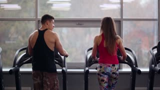 Back view of sporty man and beautiful woman walking on treadmills, talking and smiling. Work out in a sport club