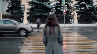 Back view. The sad young brunette girl is waiting the green light to cross the road in a winter snow-covered city.