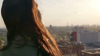 Back view. Wind blows long dark hair beautiful young women. girl standing on the roof at sunset. Slow mo