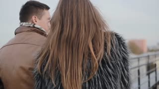 Backview of a dark-haired couple, having a walk on a roof, kissing, talking. Harmony in relationship.