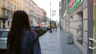 Backview of a girl at the street, flipping her hair back. Blurred background, city lights, cars, slow mo, steadicam shot