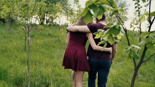 Backview of a loving couple walking in a garden. Hugging lovers enjoy nature Slow mo, steadicam shot