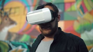 bearded attractive man a 3D Virtual Reality headset on a bright background 4k