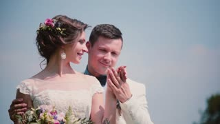 Beautiful bride is softly smiling and looking at her groom. Lovers share wedding day. Beautiful wedding accessories.