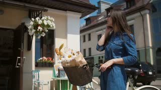 Beautiful brunette smiling girl wearing sunglasses standing near cute building with a bike talking on the phone, slow mo