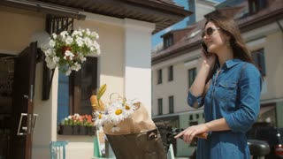Beautiful brunette smiling girl wearing sunglasses standing near cute building with bike talking on phone. 4K